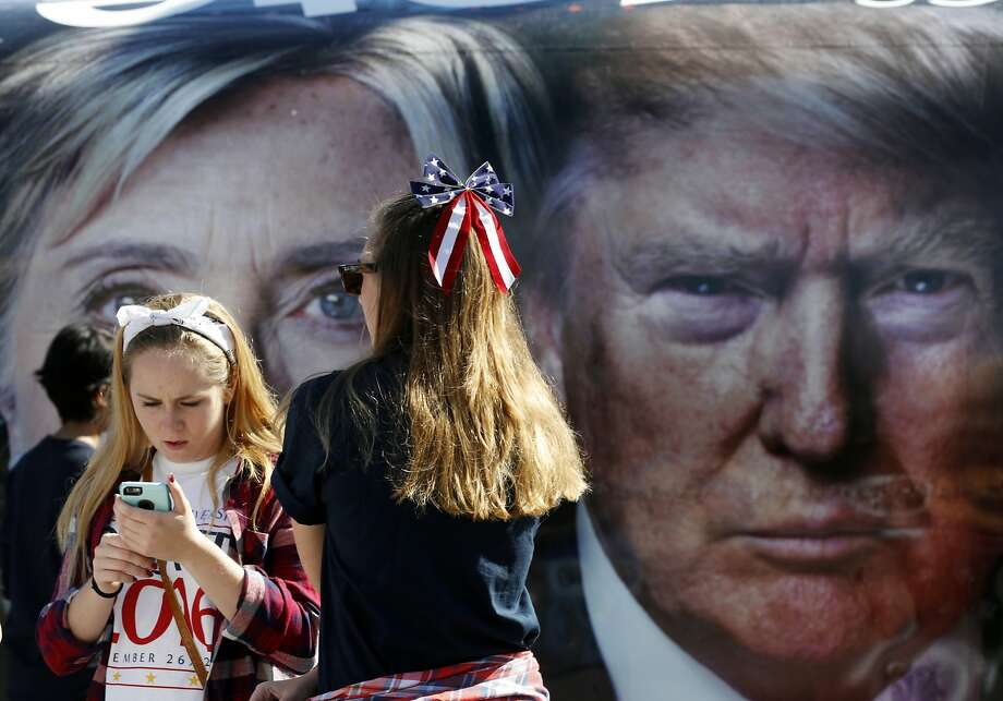 People pause near a bus adorned with large photos of candidates Hillary Clinton and Donald Trump before the presidential debate at Hofstra University in Hempstead, N.Y., Monday, Sept. 26, 2016. (AP Photo/Mary Altaffer) Photo: Mary Altaffer, Associated Press