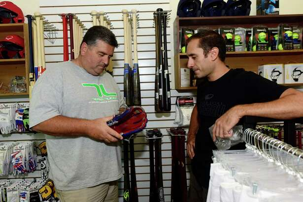 Nutmeg Sporting Goods founder Chris Carlucci, right, refurbishes a glovge for Frank Wainwright's son, at Carlucci's shop Wednesday, September 7, 2016. The shop is into its second year of business selling baseball and softball equipment and team jerseys, strategically situated below a batting cage facility on Main Ave. in Norwalk, Conn.