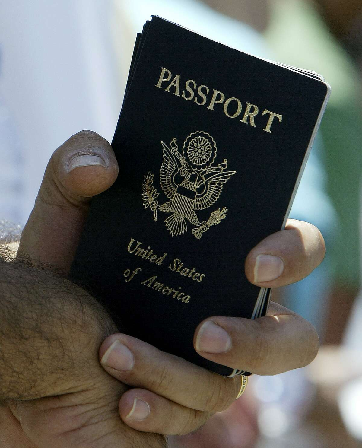 An evacuee from Lebanon holds his U.S. passport, as he waits in a line prior to his departure to the airport, at the international fairground of Nicosia, Cyprus, Thursday, July 20, 2006. Some 900 U.S. citizens, many of them of Lebanese origin, arrived on the cruise liner Orient Queen early Thursday, completing the first trip in a massive operation to evacuate thousands of U.S. citizens from wartorn Lebanon. (AP Photo/Thanassis Stavrakis)