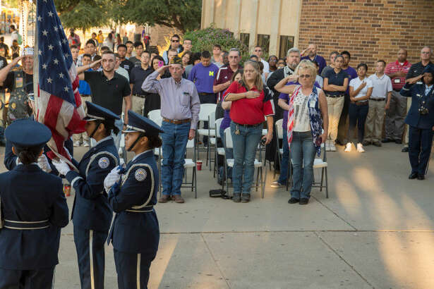 The crowd stands at attention as the Midland High JROTC Honor Guard raises the flag Sept. 9 at the Sept. 11 Memorial ceremony. More women are being involved in JROTC at both Midland and Lee high schools.