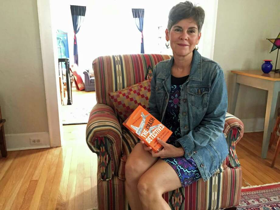 "Christine Negroni holds a copy of her new book, ""The Crash Detectives: Investigating the World's Most Mysterious Air Disasters,"" at her home in Greenwich. Photo: Peregrine Frissell / Hearst Connecticut Media / Greenwich Time"