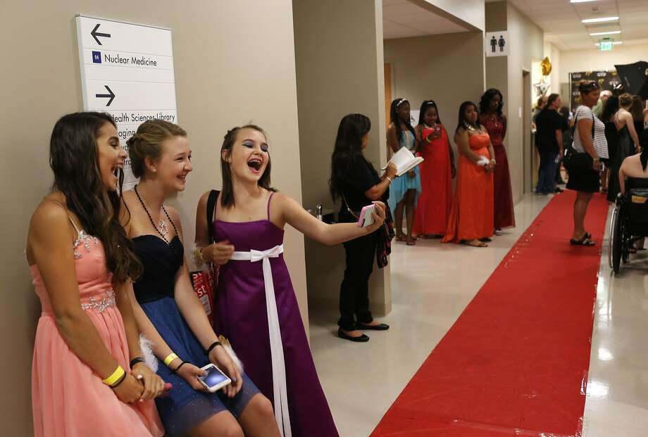 From left, Isabel Cervantes, 13, Camryn Taft, 13, and Nomi Solwren, 13, take a group selfie in the hallway during Kaiser Permanente Oakland's Pediatric Prom at Oakland Medical Center Sept. 24, 2016 in Oakland, Calif. The second annual dance was attended by around 100 teens who were otherwise unable to have the traditional school dance experience due to trauma or illness. Photo: Leah Millis, The Chronicle