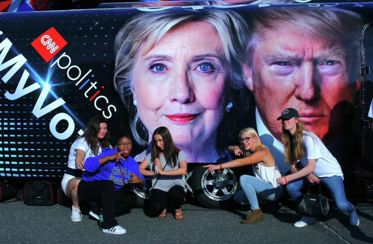 Students pose for a pictures next to a banner outside the hall where the first presidential debate at Hofstra University's David & Mack Sport and Exhibition Complex in Hempstead, New York on September 26, 2016. The first US presidential debate, between Democratic candidate Hillary Clinton and Republican Donald Trump, is one of the high points of the campaign, six weeks from the November 8 elections. / AFP PHOTO / KENA BETANCURKENA BETANCUR/AFP/Getty Images
