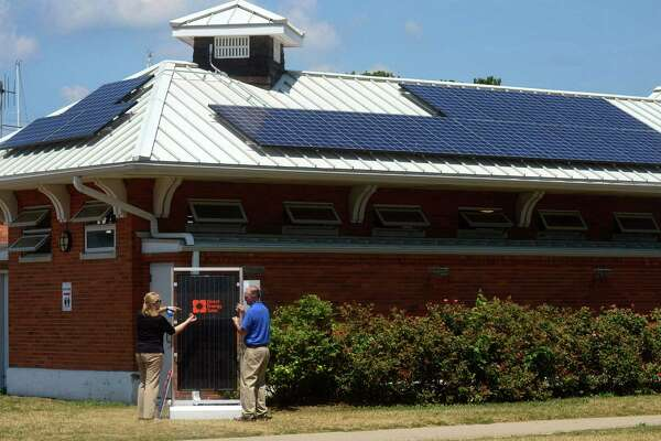 Direct Energy Solar staff including Community Program Specialist, Dana Rye, and Senior Project Lead, Mike Brooks, set up a ceremonial switch for the new solar panels on the bath houses at Calf Pasture Beach in Norwalk, Conn. before a press conference there Wednesday, July 6, 2016.