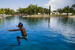Dean Strong, 8, jumps into the crystal clear waters of the worlds largest spring-fed swimming pool in his snorkeling gear at Balmorhea State Park Friday, Sept. 16, 2016 four miles west of Balmorhea in Toyahvale, TX. Houston-based Apache Corporation recently announced the discovery of an estimated 15 billion barrels of oil and gas in the area and plans to drill and use hydraulic fracturing on the 350,000 acres surrounding the park. Apache has leased the mineral rights under the park and town, but has promised not to drill on or under either. Even with the promises, some residents worry that the drilling could affect the 15 million gallons of water that flow through the pool every day and impact the more than 200,000 visitors the pool attracts annually. ( Michael Ciaglo / Houston Chronicle )