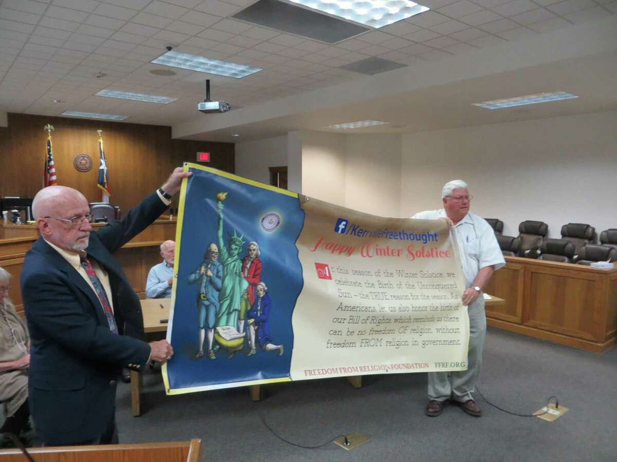 Kerrville Freethought representative David Whitsett (left) and Kerr County Judge Tom Pollard show what the banner that Whitsett wanted hung outside the courthouse looks like back in September, when county commissioners rejected the request. Another vote Monday had the same result, though Pollard this time voted in favor, predicting the county would lose in court.