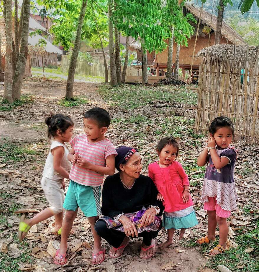 The extended family of Phad, a guide at the Gibbon Experience in Laos, assembles to wish zip liners well as they begin a hike into the forest. / The Washington Post