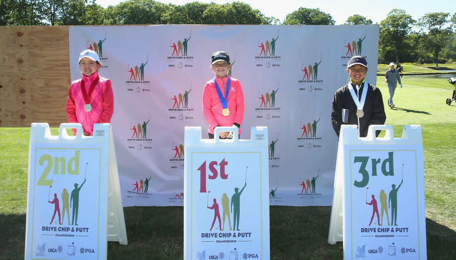 BROOKLINE, MA - SEPTEMBER 25: First place winner Kennedy Swedick (C), second place winner Sarah Shao (L), and third place winner Nicole Yugay (R) in the girls 10-11 Overall Competition stand with their medal during a regional round of the Drive, Chip, and Putt Championship at The Country Club on September 25, 2016 in Brookline, Massachusetts. (Photo by Billie Weiss/Getty Images for DC&P Championship/Getty Images)