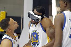 Stephen Curry (30) and Kevin Durant (35) walks up on an unsuspecting Andre Iguodala (9) as he uses a virtual reality headset during Warriors Media Day at their training facility in Oakland, Calif., on Monday, September 26, 2016.