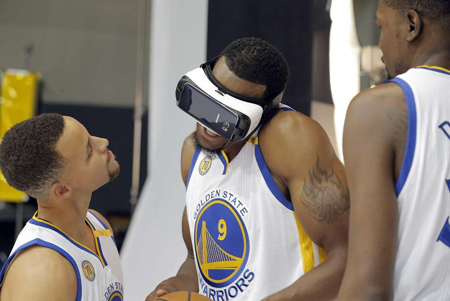 Stephen Curry (30) and Kevin Durant (35) walks up on an unsuspecting Andre Iguodala (9) as he uses a virtual reality headset during Warriors Media Day at their training facility in Oakland, Calif., on Monday, September 26, 2016. Photo: Carlos Avila Gonzalez / The Chronicle