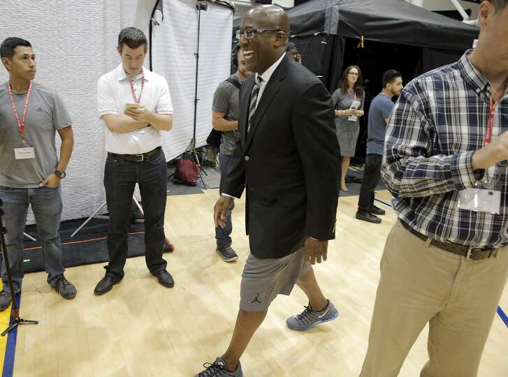 Assistant Coach Mike Brown walks away after having his photo taken wearing a blazer and his training shorts during Warriors Media Day at their training facility in Oakland, Calif., on Monday, September 26, 2016.
