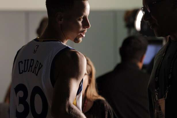 Stephen Curry (30) is interviewed by Marc Spears of ESPN as they walk to Curry's next session during Warriors Media Day at their training facility in Oakland, Calif., on Monday, September 26, 2016.