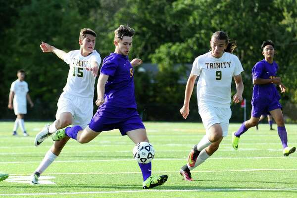 Westhill junior Casey Ottaviano gets a shot off while under pressure from Trinity Catholic players Matt Hennessey (15) and Alex Romanczuk (9) during a game at Gaglio Field in Stamford, Conn. on Monday, Sept. 26, 2016.