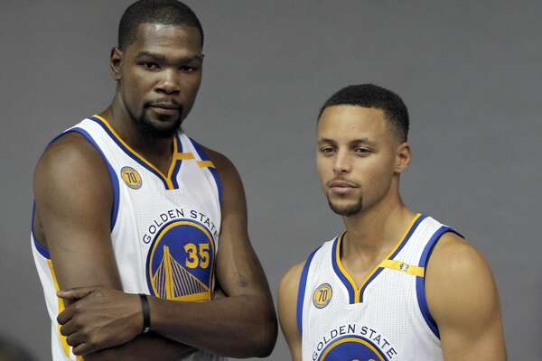 Kevin Durant (35) and Stephen Curry (30) pose for a photo during Warriors Media Day at their training facility in Oakland, Calif., on Monday, September 26, 2016.