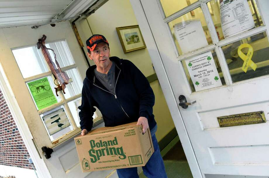 Town Judge Richard Snyder carries bottled water from a distribution center on Saturday, Feb. 20, 2016, at the Petersburgh Town Hall in Petersburgh, N.Y. Snyder planned to deliver water to the Baptist and Methodist churches in town so they could make coffee in the morning. (Cindy Schultz / Times Union) Photo: Cindy Schultz / Albany Times Union