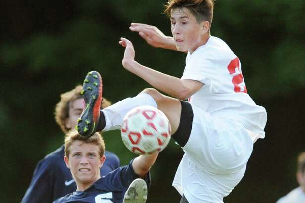 Staples' Jannis Dietz and airborne Greenwich player Nicholas Hickman battle for the ball in the high school boys soccer game between Greenwich and Staples at Greenwich High School in Greenwich, Conn. Monday, Sept. 26, 2016. The game ended in a 0-0 draw.