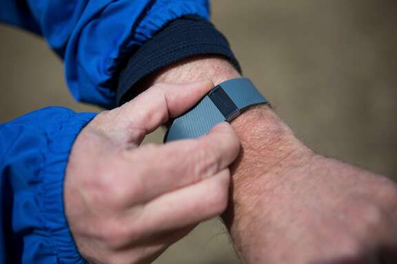 FILE -- Michael Doughty sets his Fitbit wristband prior to his run in Boston, April 6, 2016. Dieting adults who wore activity monitors for 18 months lost significantly fewer pounds over that time than those who did not. (Charlie Mahoney/The New York Times)