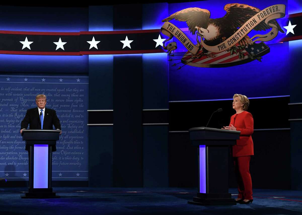 Republican nominee Donald Trump looks on as Democratic nominee Hillary Clinton speaks during the first presidential debate at Hofstra University in Hempstead, New York on September 26, 2016. / AFP PHOTO / Jewel SAMADJEWEL SAMAD/AFP/Getty Images