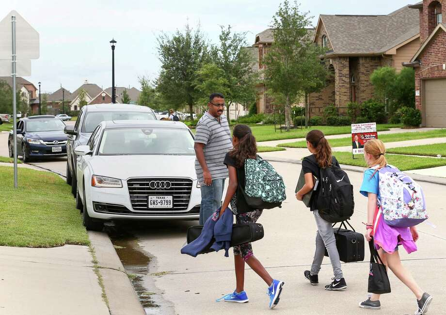 Aby Mattathu, left, picks up his daughter, Tanya Philip,  second from left, and her two friends after school Friday, Sept. 23, 2016, in Katy. Mattathu is pushing Katy ISD to provide bus service to his neighborhood. Photo: Jon Shapley, Houston Chronicle / © 2015  Houston Chronicle