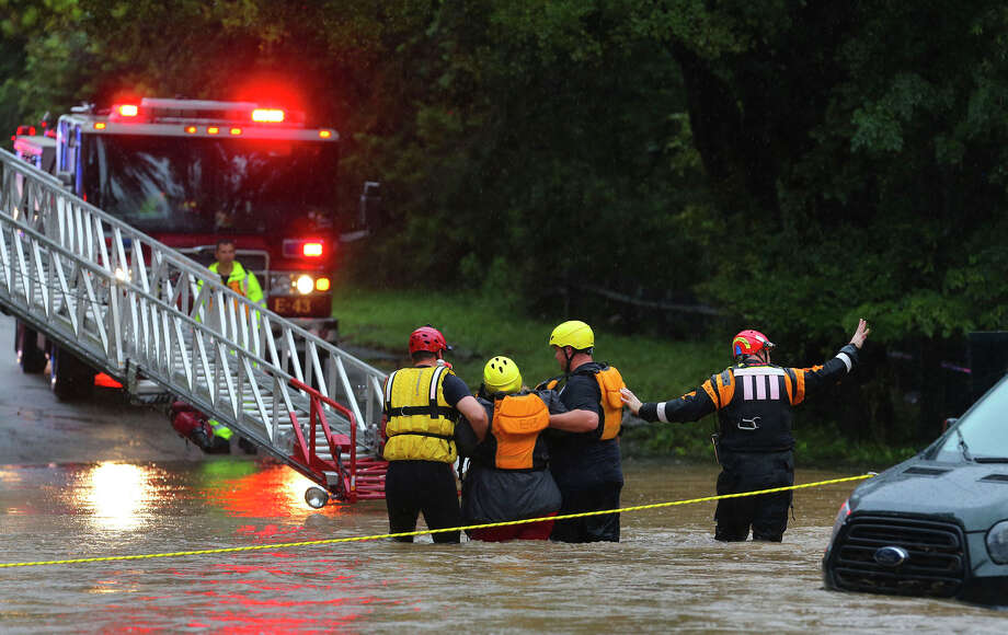 Firefighters rescue one of five people from a van that was trapped in high water in the 1300 block of George Road on the Northwest Side. A Fire Department spokesman said there were about 40 high-water incidents reported between 5 and 9:30 a.m. Photo: John Davenport /San Antonio Express-News
