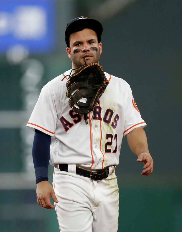 Houston Astros Jose Altuve (27) holds his glove in his teeth after he was injured diving for Seattle Mariners third baseman Kyle Seager's single in the sixth inning of an MLB game at Minute Maid Park, Monday, Sept. 26, 2016 in Houston. Photo: Karen Warren, Houston Chronicle / 2016 Houston Chronicle