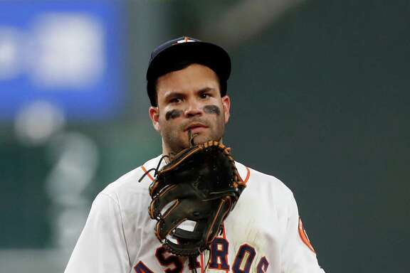 Houston Astros Jose Altuve (27) holds his glove in his teeth after he was injured diving for Seattle Mariners third baseman Kyle Seager's single in the sixth inning of an MLB game at Minute Maid Park, Monday, Sept. 26, 2016 in Houston.