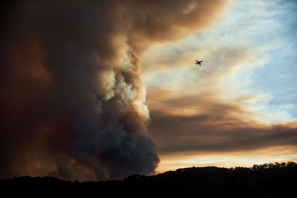 An aircraft circles a smoke column as the Loma fire burns northwest of Morgan Hill, Calif., on Monday, Sept. 26, 2016.