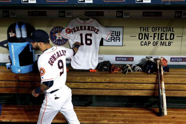 Marwin Gonzalez touches the jersey the Astros placed in their dugout to honor late Marlins pitcher Jose Fernandez.