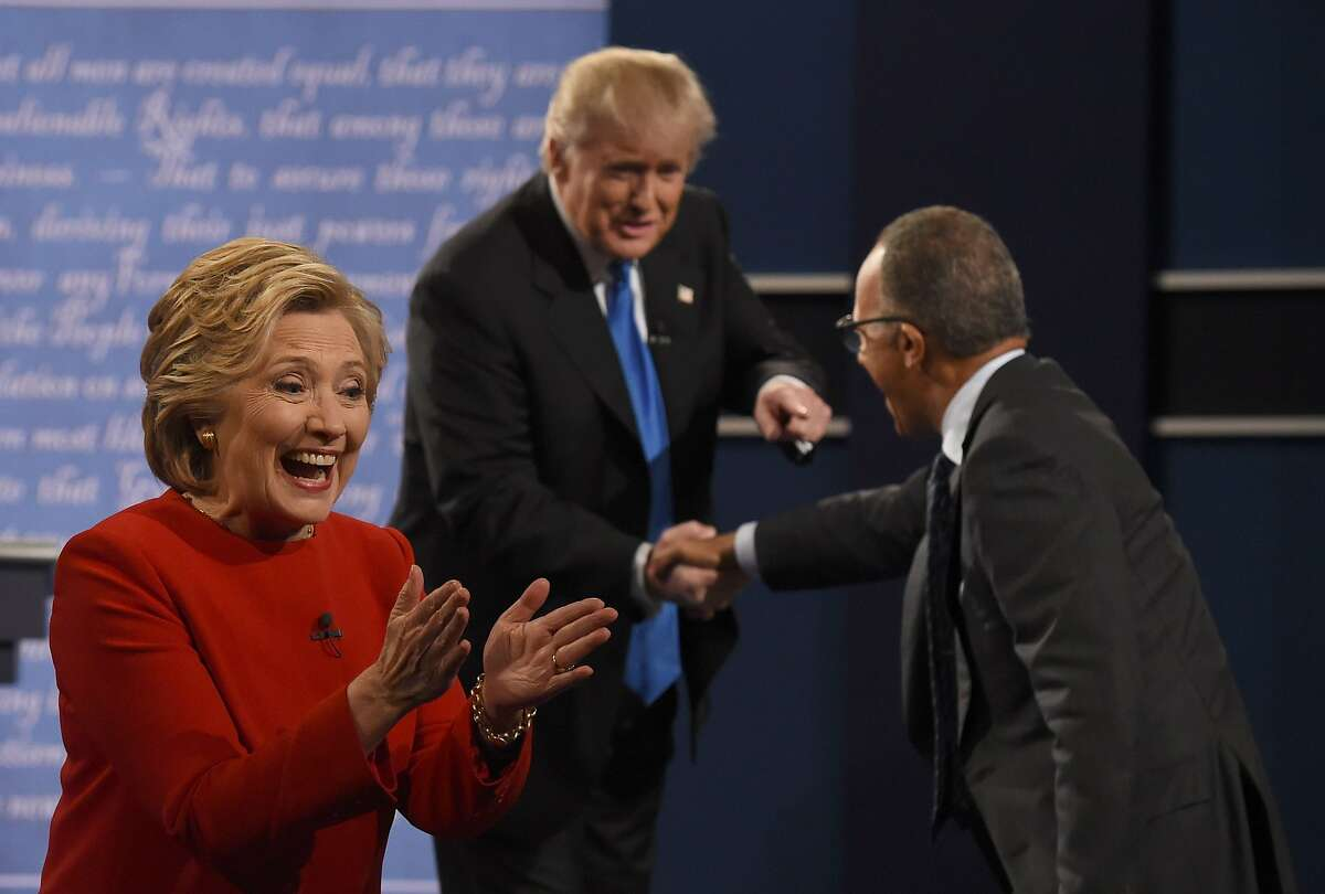 Democratic nominee Hillary Clinton reacts as Republican nominee Donald Trump (C) shakes the hand of debate moderator Lester Holt after the first presidential debate at Hofstra University in Hempstead, New York on September 26, 2016. / AFP PHOTO / Timothy A. CLARYTIMOTHY A. CLARY/AFP/Getty Images