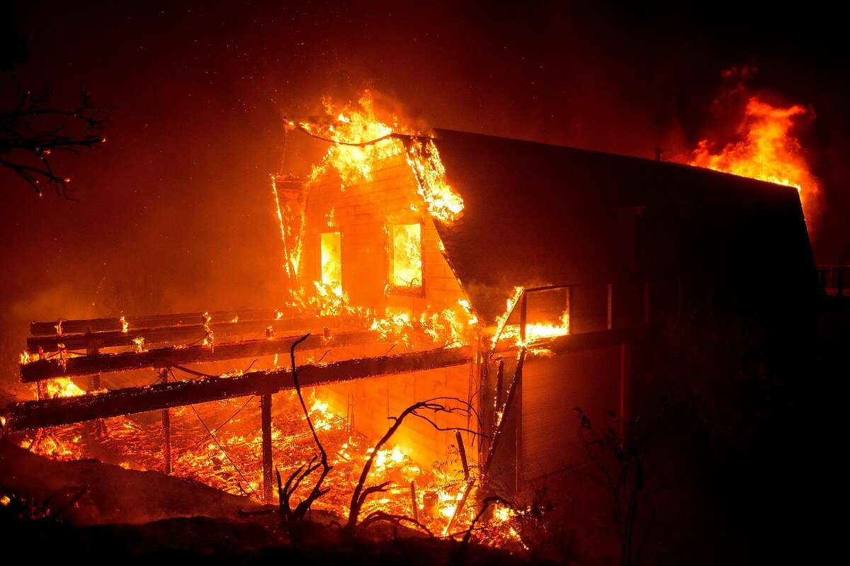 Flames consume a structure on Loma Chiquita Road as the Loma fire burns northwest of Morgan Hill, Calif., on Monday, Sept. 26, 2016.