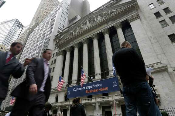 FILE - In this Oct. 2, 2014, file photo, people pass the New York Stock Exchange. Stock markets around the world fell sharply Monday, Sept. 26, 2016, as investors turned their attention to the U.S. presidential race and the first televised debate between Hillary Clinton and Donald Trump. (AP Photo/Richard Drew, File)