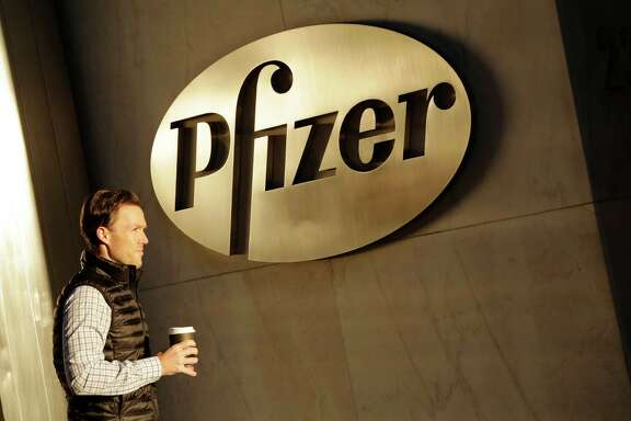 FILE - In this Monday, Nov. 23, 2015, file photo, a man enters Pfizer's world headquarters, in New York. Pfizer will not split into two publicly traded companies, a decision that, at least for now, ends Wall Street speculation over the drugmaker's future. The company believes it is best positioned to maximize shareholder value in its current form, but said Monday, Sept. 26, 2016, that it's reserving the right to split in the future if the situation changes. (AP Photo/Mark Lennihan, File)