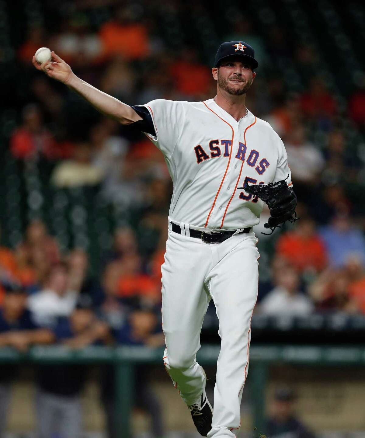Houston Astros relief pitcher James Hoyt (51) makes a throwing error as he tried to get Seattle Mariners Norichika Aoki (8) out at first base creating a run scored to tie the game in the ninth inning of an MLB game at Minute Maid Park, Monday, Sept. 26, 2016 in Houston.