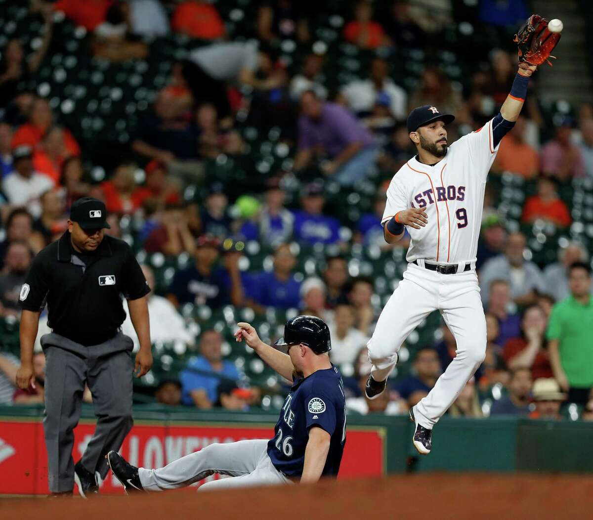 Houston Astros third baseman Marwin Gonzalez (9) tries to get the tag on Seattle Mariners Adam Lind (26) at third base in the second inning of an MLB game at Minute Maid Park, Monday, Sept. 26, 2016 in Houston. ( Karen Warren / Houston Chronicle )