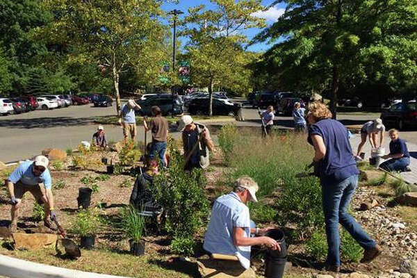 Volunteers with Save the Sound help build a rain garden to capture storm water run off at the Beardsley Zoo on Saturday, Sept. 24, 2016.