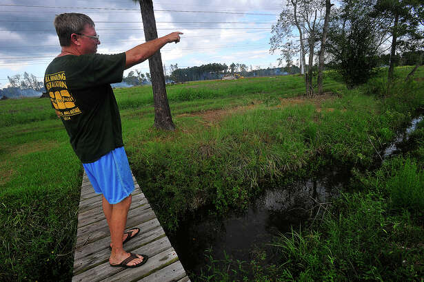West Chasse resident Brian Davis points out the spot where flooding problems begin along the drainage ditch that runs behind his home in the Orange subdivision.  Flooding has occurred since developer Sam Peveto began working on clearing a large parcel of land north of the neighborhood and connecting drainage from his land into the ditch. The City of Orange has filed an injunction that Peveto stop work on the drainage ditch that runs in-between the properties. They say routing water from his site into the ditch is overloading it, which has resulted in flooding of the road on the far west end of the subdivision. Home owners are concerned that heavier rainfalls could result in water eventually making its way into their houses. Photo taken Friday, September 23, 2016 Kim Brent/The Enterprise