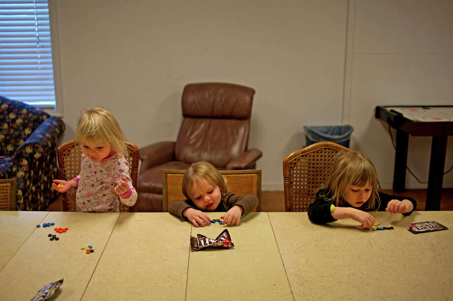 From left: Savanna Hulbert, 2, Brianna Hulbert, 1, and Scotland Klein, 5, count and organize their M&M's at Midland's Open Door House of Mercy women's shelter in this 2015 file photo.