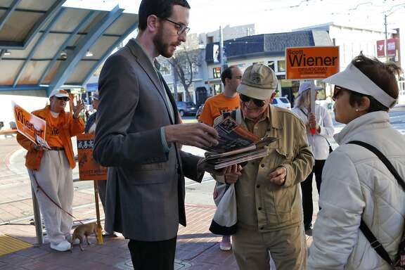 Roger Ritter, President of West of Twin Peaks Central Council, center, talks to Supervisor Scott Wiener about crime and public safety concerns as Mary Ritter, Roger's wife, listens at right, while Wiener campaigs at the West Portal Muni stop Sept. 23, 2016 in San Francisco, Calif.