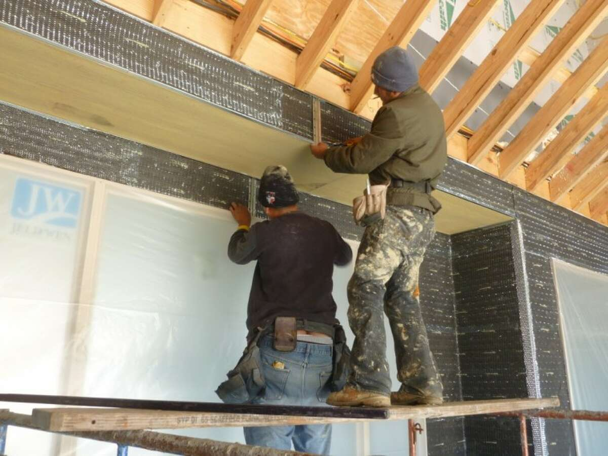 A crew works on a custom home in a Spring community.
