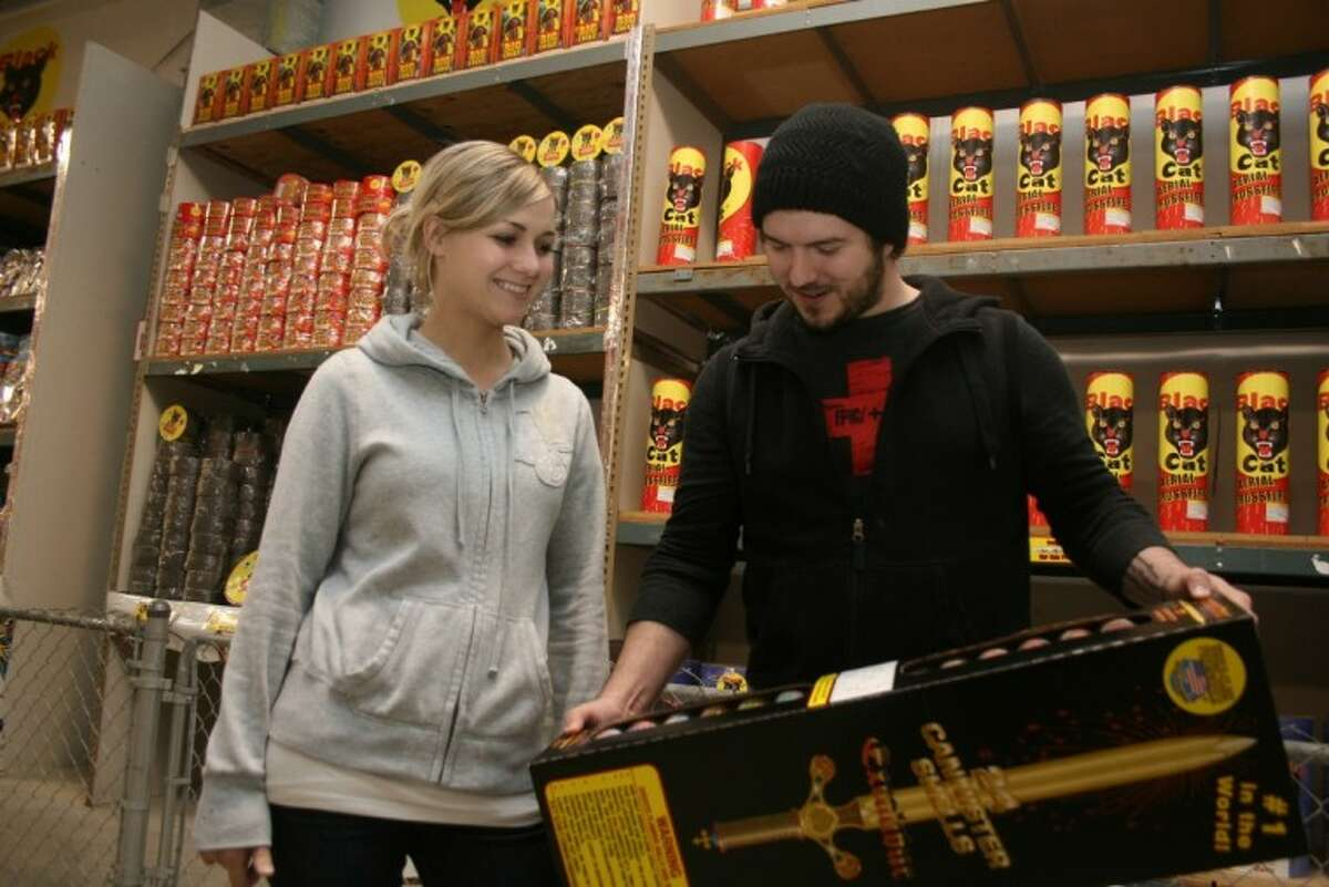 Youth Pastor Justin Merando shows his wife some of the specialty fireworks offered at the TopDog Fireworks Warehouse. This is the fourth season Crosby Church has ran the warehouse.
