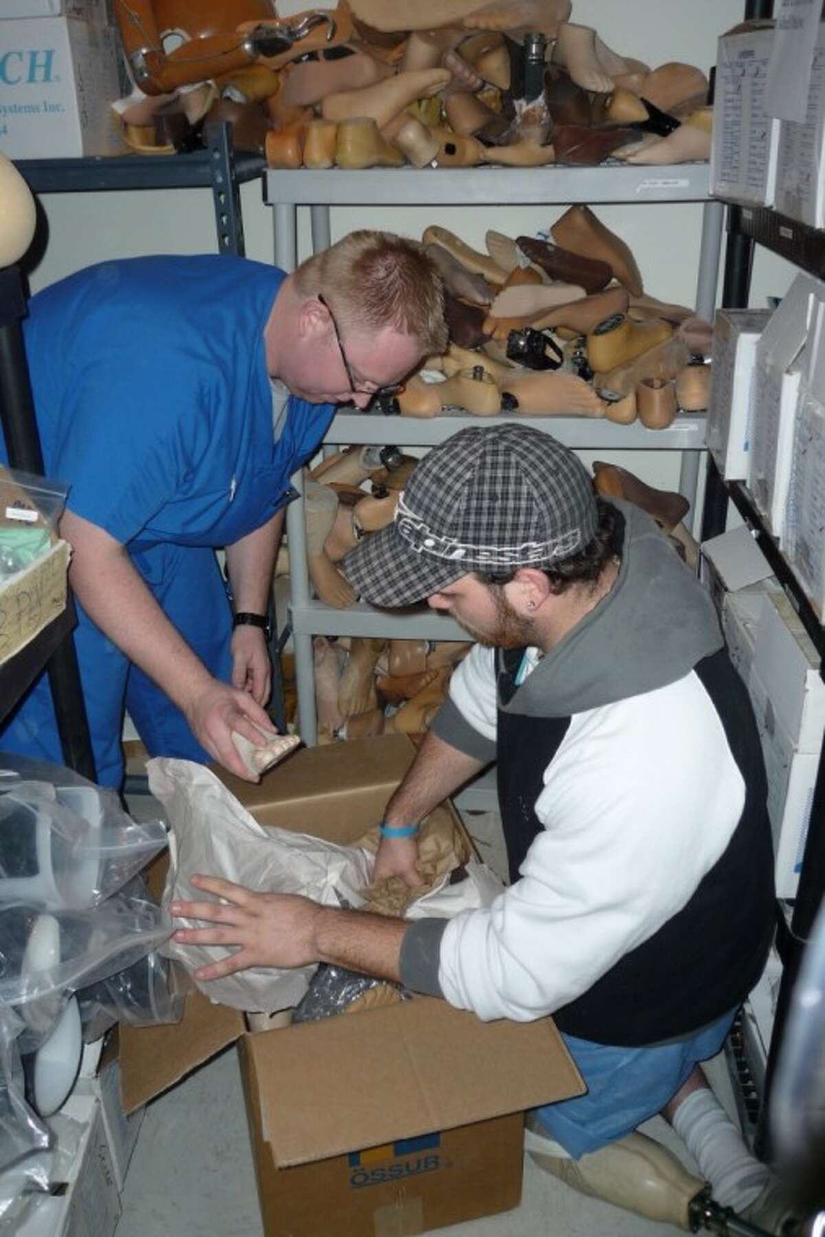Amputee & Prosthetic Center employees Nick Glebowski and Aaron Johnson pack prosthetic components to send to people that lost limbs in Haiti's earthquake.