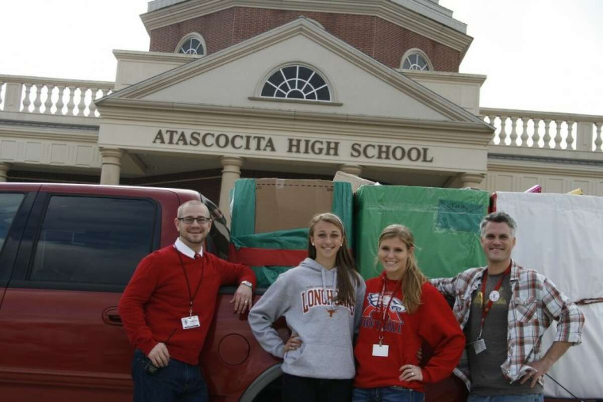 From left, Atascocita High assistant principal Matt Roser, student Brooke Kirchhofer, student Kristin Hebert and District Service Learning Coordinator and Campus Social Action teacher Kap McWhorter pose in front of all of the toys collected for children at HAAM and FamilyTime Crisis and Counseling Center.