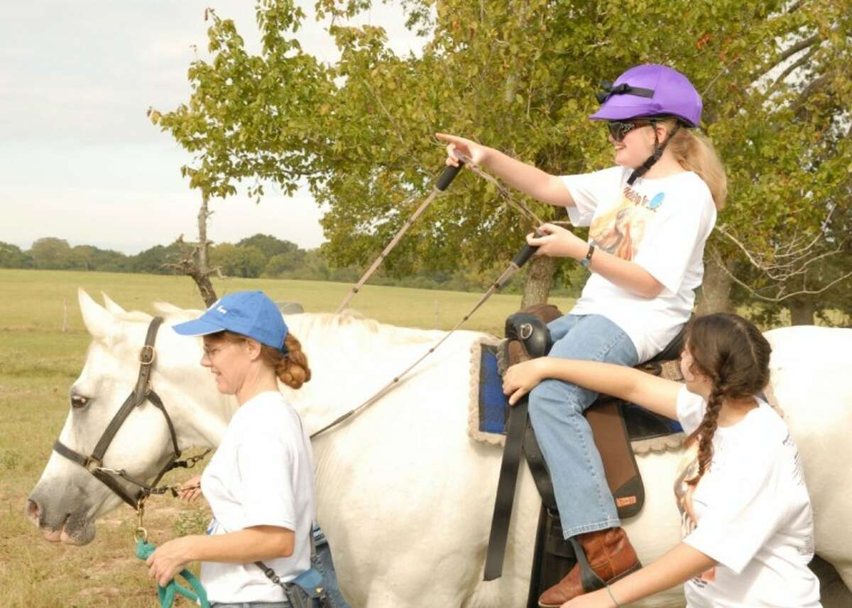 Casey Aulenbach rides a horse named Pal at the SIRE Ride-a-Thon. Sire is a therapeutic equestrian center that caters to helping children and adults with disabilities.