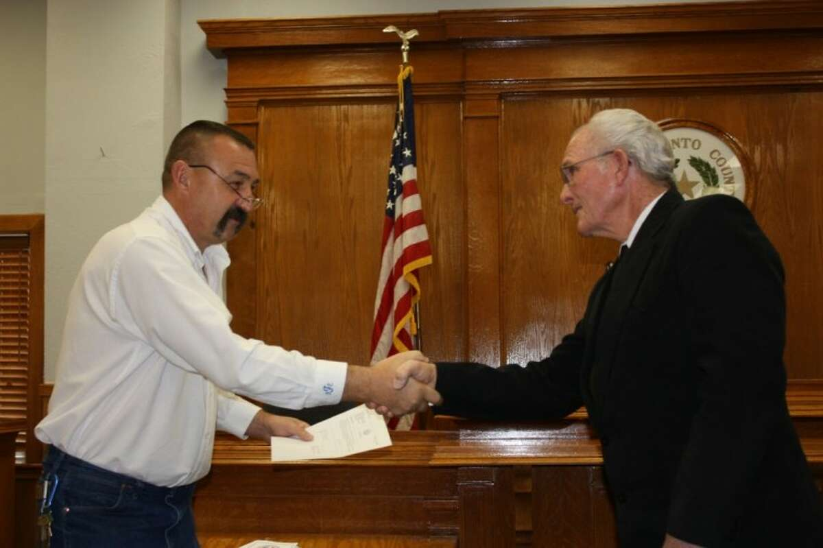 San Jacinto County Judge Fritz Faulkner, left, congratulates newly-elected Pct. 3 Commissioner Thomas Bonds, right after taking his oath of office.