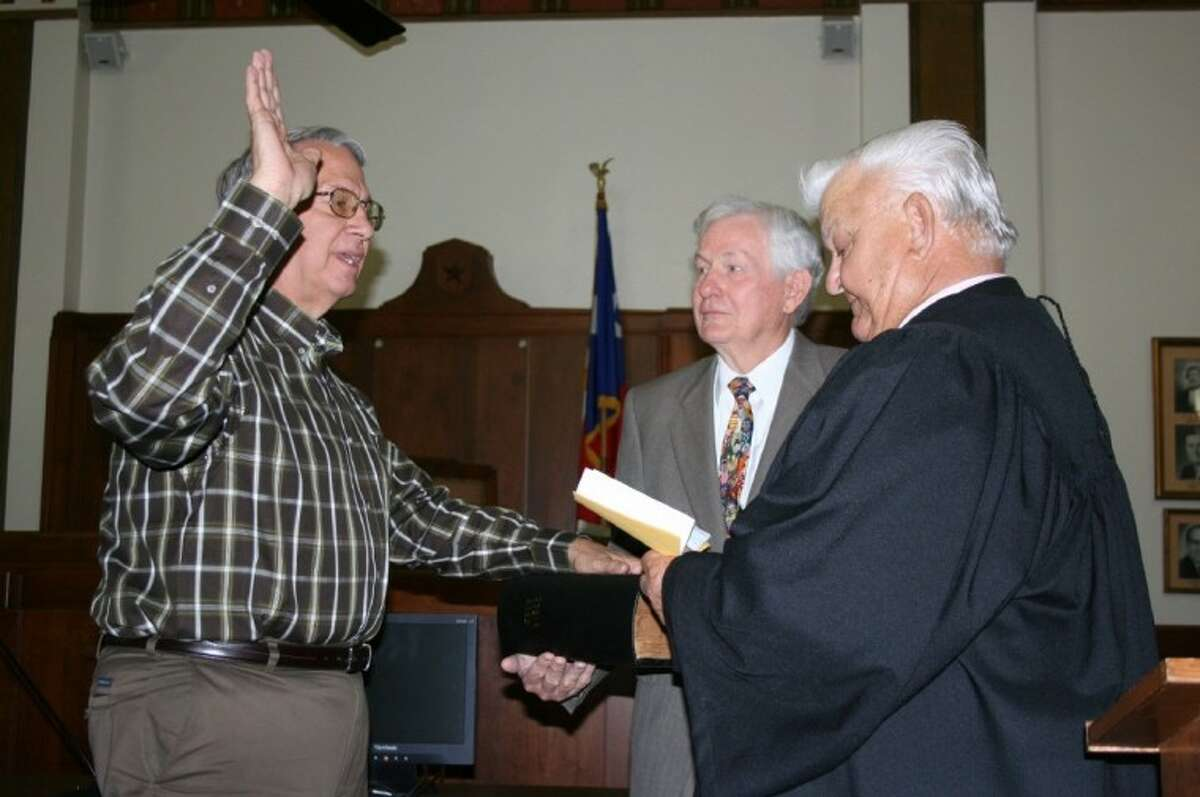 Bobby Rader (left) chose two men he said were his mentors - former Liberty County Court at Law Judge Don Taylor (center) and Pct. 2 Justice of the Peace Ronnie Davis (right) - to administer his oath of office as the new sheriff for Liberty County. The swearing-in ceremony was held Jan. 2, 2013, in the 75th District Courtroom at the Liberty County Courthouse