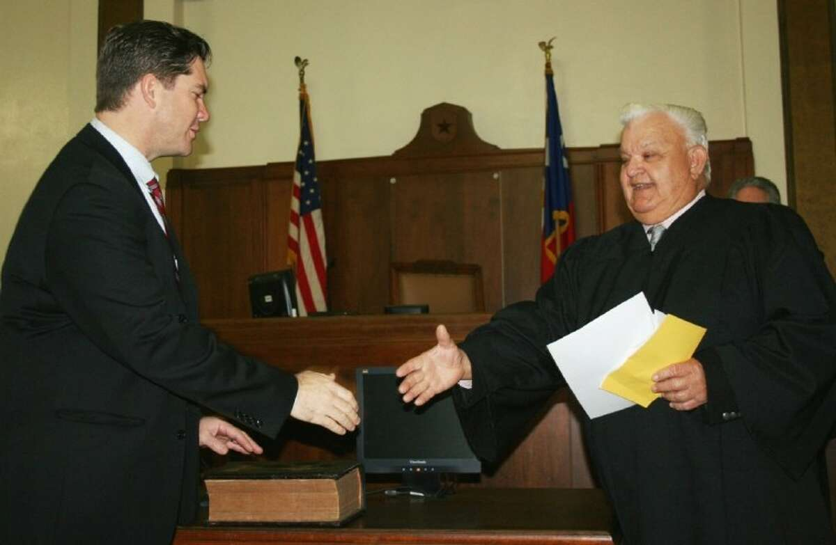 Liberty County Attorney Wes Hinch (left) accepts congratulations from Pct. 2 Justice of the Peace Ronnie Davis, who administered Hinch's oath of office at a ceremony on Jan. 2, 2013, in the 75th District Courtroom at the Liberty County Courthouse.