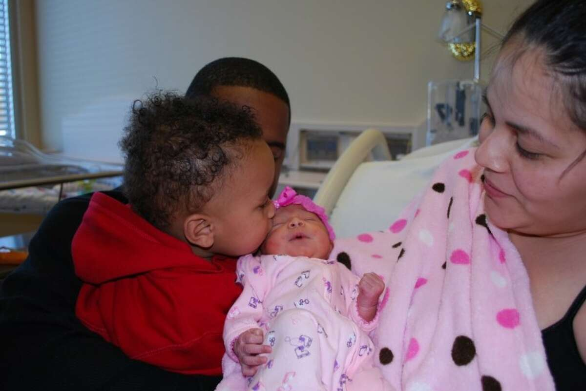 Big brother Kamari, 11 months, plants a kiss on new baby sister KaMyira, the first baby born in 2011 at Christus St. John Hospital in Nassau Bay.