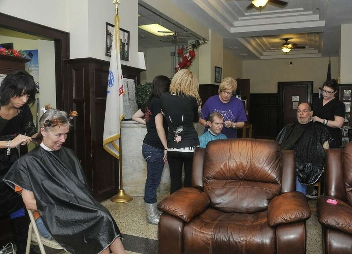 Cosmetology students Karla Flores (left) and Laura Richardson (far right) give free haircuts to DeGeorge residents Sandy Harford (sitting left) and Michael Berryman (sitting far right). December 2012_CosmetologyVeterans2: Cosmetology student Lindsey Vice gives veteran Taiyan Hamilton a facial in the South Campus spa classroom.