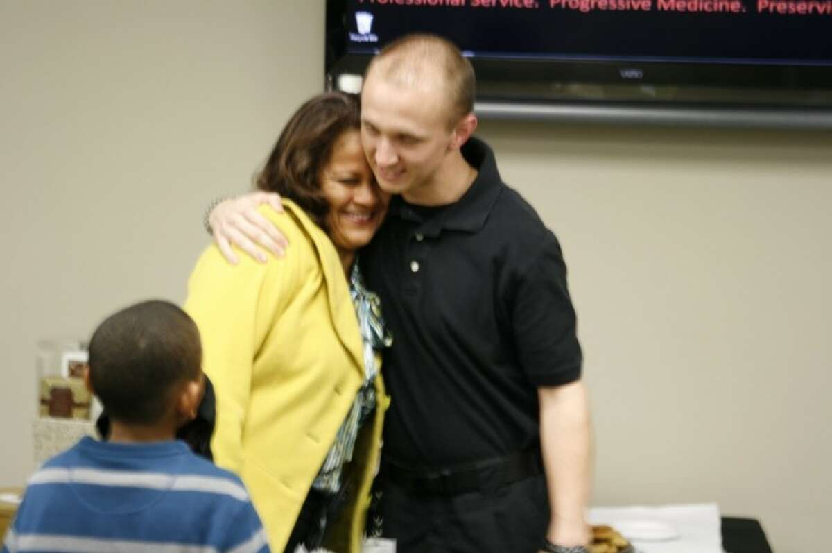 Rita Jolivet receives a hug from ESD 1 dispatcher Tyler Pursell as her son Treyvion Fontenot looks on. Jolivet recently was reunited with the emergency crews who saved her life after her son called 911 when she was suffering a heart attack about two weeks ago.