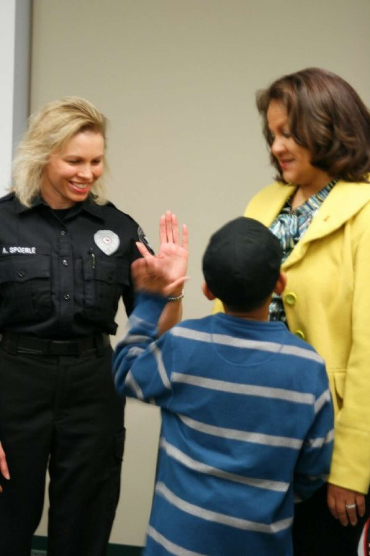 ESD 1 paramedic Amy Spoerle gives Treyvion Fontenot a high five during the reuniting ceremony Dec. 29. Fontenot called 911 after his mother had a heart attack about two weeks ago.